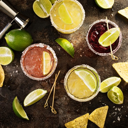 Variety of margarita cocktails with salted rim and lime on dark background overhead shot Foto de archivo