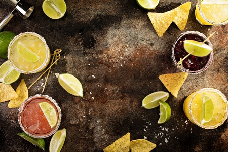 Variety of margarita cocktails with salted rim and lime on dark background overhead shot with copy space Stock Photo