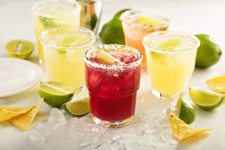 Variety of margarita cocktails with salted rim and lime on white background