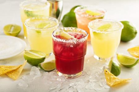 Verscheidenheid van Margarita-cocktails met gezouten rand en kalk op witte achtergrond