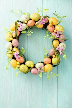 Easter eggs wreath on light blue background