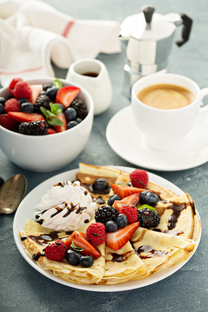 Thin crepes with whipped cream and berries