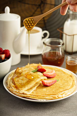 Thin crepes with strawberry and honey Stock Photo