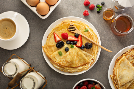 Thin crepes with berries and honey Stock Photo