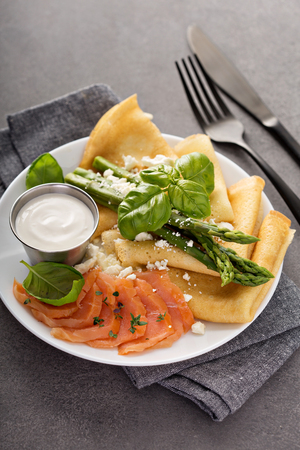 Savory crepes with salmon, sour cream and asparagus Stock Photo