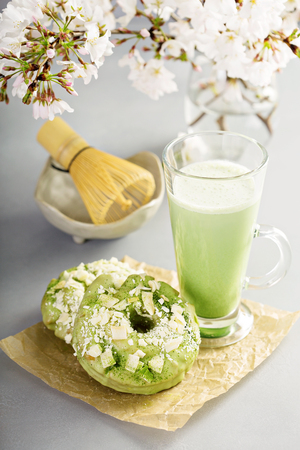 Matcha and white chocolate donuts with tea Stock Photo