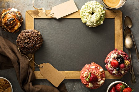 Variety of donuts around a chalkboard Banco de Imagens