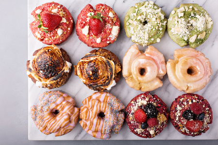 Variety of colorful old fashioned fried gourmet donuts on a marble surface with glaze Stock Photo