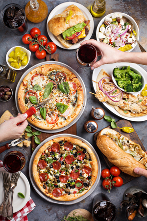 Big dinner with pizza, salad and sandwiches with hands reaching food overhead view