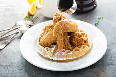 Fried chicken and waffles with syrup pouring, southern food concept Banco de Imagens