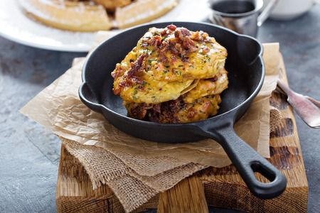 Fried green tomatoes with cheese and bacon in cast iron pan