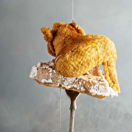 Fried chicken wing with a waffle on a fork with syrup pouring over, southern food concept