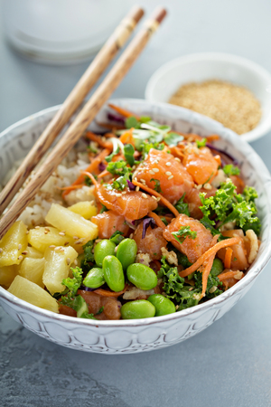 Poke bowl with raw salmon, rice and vegetables