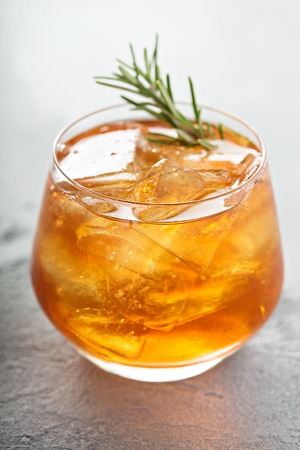 Old fashioned cocktail with ice and rosemary