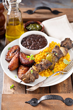 Beef kebab with rice, beans and fried plantains