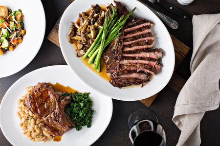 Overhead shot of a dinner table with steak and grilled pork