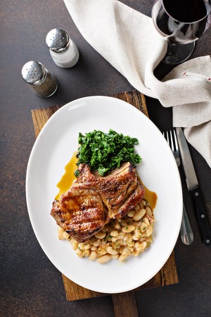 Grilled pork chop with cassoulet and braised greens