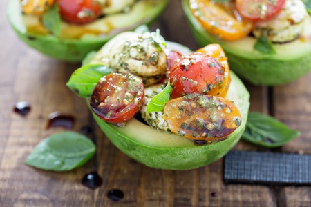 Avocado stuffed with pesto caprese salad
