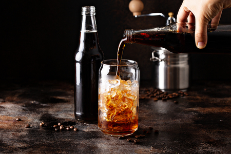 Cold brew iced coffee in glass bottles being poured over ice 스톡 콘텐츠 - 110714419