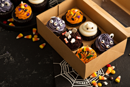 Halloween cupcakes with variety of decorations in a to go box