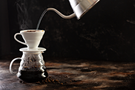Making pour over coffee with hot water being poured from a kettle