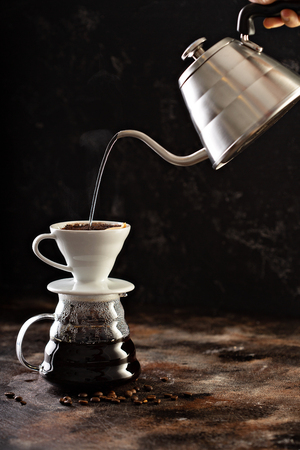 Making pour over coffee with hot water being poured from a kettle Фото со стока - 114550870