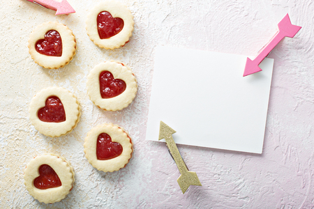 Heart shaped vanilla cookies with jam filling for Valentines day with a blank card copy space