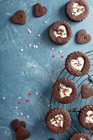 Heart shaped chocolate cookies with cream filling for Valentines day on a baking rack, sweet treats background