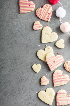 Heart shaped cookies for Valentines day with pink glaze, overhead shot with copy space Stock Photo