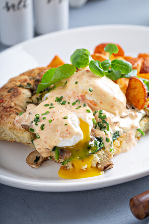 Eggs Benedict with focaccia and potatoes Stock Photo