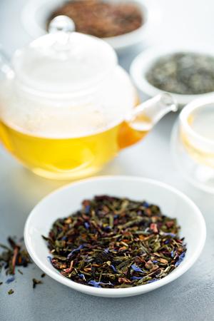 Green loose leaf tea and a teapot Stock Photo
