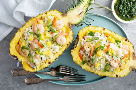 Shrimp rice with green onions served in pineapple boats Standard-Bild