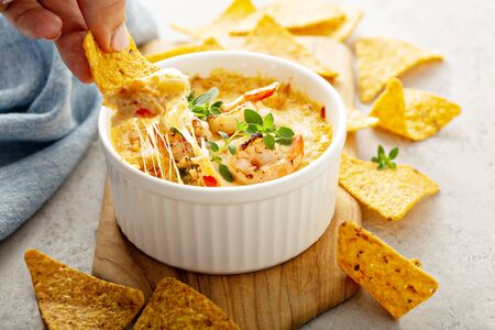 Spicy seafood dip in a ramekin with corn chips Stockfoto