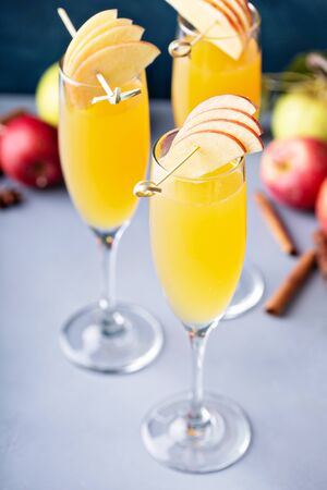 Apple mimosa cocktail in tall flute glasses, fall drinks
