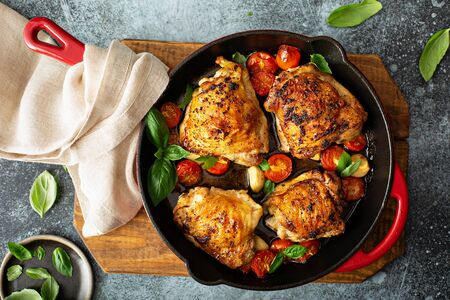 Chicken thighs roasted with tomatoes and garlic Banco de Imagens