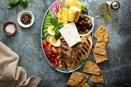 Grilled chicken platter with vegetables, grilled corn, eggs and feta cheese, greek inspired lunch