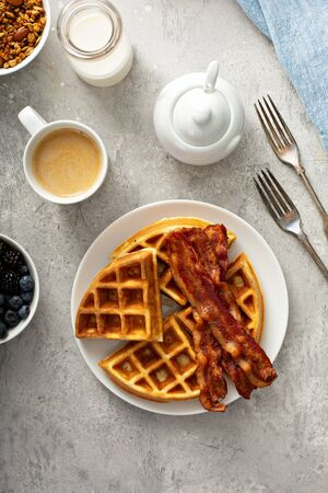 Breakfast plate on the table with waffles and bacon, berries and maple syrup Stockfoto