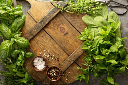 Assorted fresh herbs and spices on a wooden board, cooking background