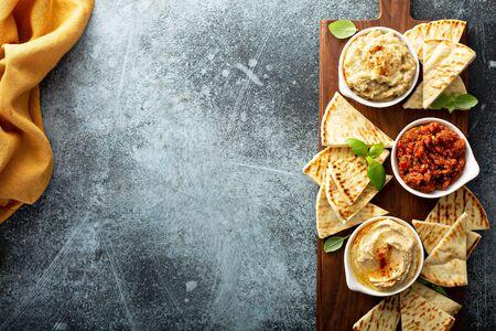 Mediterranean mezze board with pita, hummus, tomato dip and baba ganoush