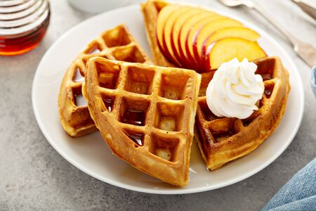 Peach waffles for breakfast served with fresh berries, maple syrup and coffee Banco de Imagens