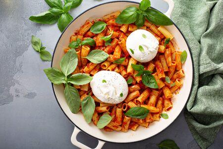 Penne pasta marinara with buratta cheese and fresh basil Stok Fotoğraf