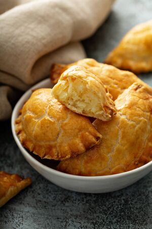 Hand pies, pasties, samosas or pierogies with potato filling golden baked Imagens