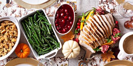 Thanksgiving dinner table with sliced turkey and sides, overhead shot