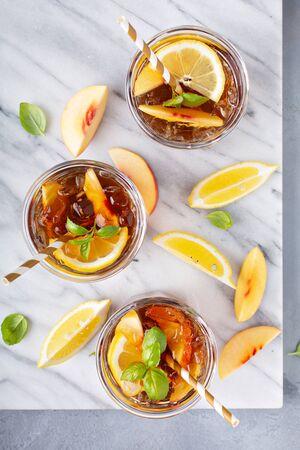 Peach and lemon sweet iced tea on a marble surface overhead shot