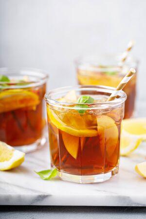 Peach and lemon sweet iced tea on a marble surface