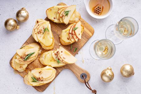 Pear and brie crostini with honey, pecan and rosemary, New Years Eve or Christmas party appetizer Stock Photo