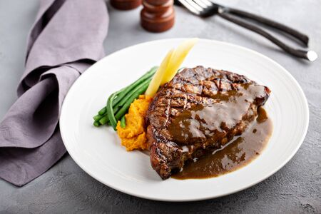 Grilled beef steak with gravy and vegetables Stock Photo