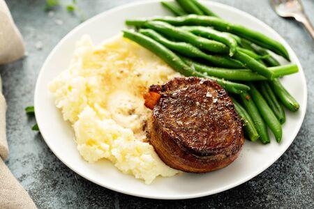 Traditionelles Abendessen mit einem mit Speck umwickelten Steak, grünen Bohnen und Kartoffelpüree