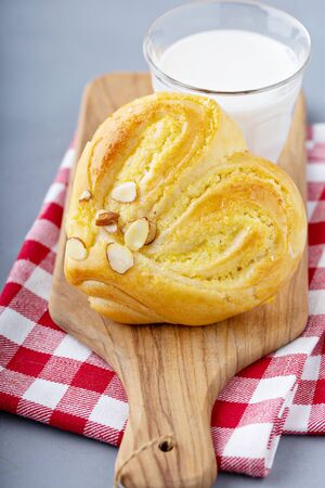 Heart shaped pastry or sweet roll with milk, romantic treat for Valentines day