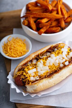 Chili hot dog topped with cheese and onion, served with sweet potato fries 版權商用圖片
